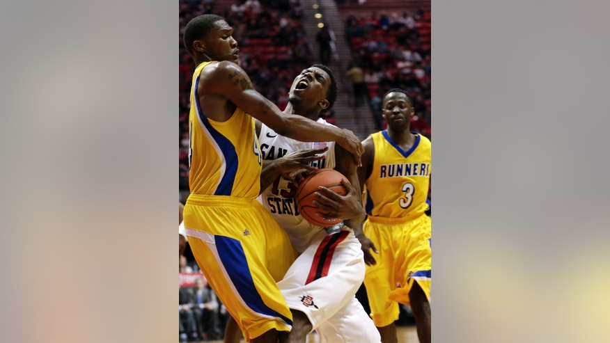 San Diego State's Winston Shepard, center, drives and picks up a foul by Cal State Bakersfield's Stephon Carter, left, as Javonte Maynor (3) looks on at right in the second half during an NCAA college basketball game Wednesday, Jan. 2, 2013, in San Diego. (AP Photo/Gregory Bull)
