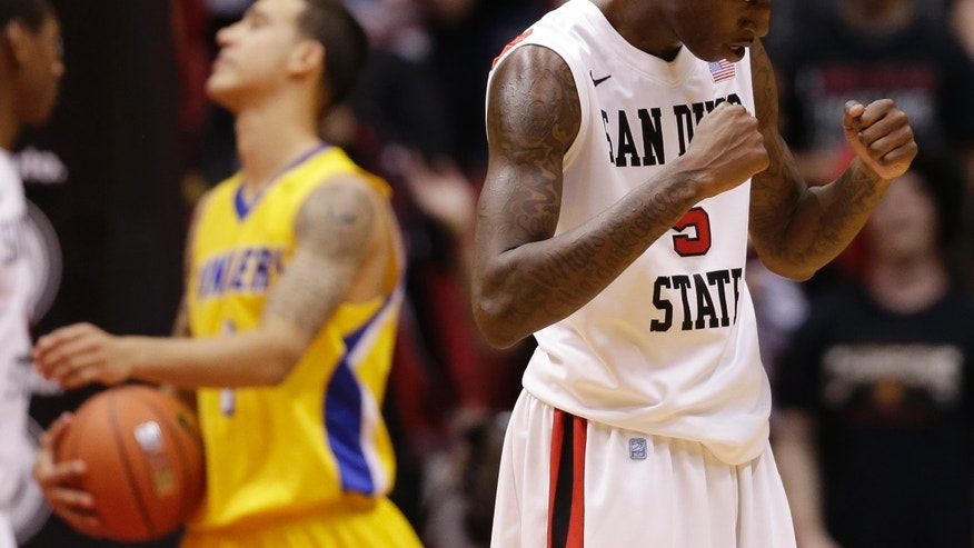 San Diego State's Dwayne Polee, right, reacts after picking up a foul as Cal State Bakersfield's Tyrone White passes behind in the second half during an NCAA college basketball game Wednesday, Jan. 2, 2013, in San Diego. (AP Photo/Gregory Bull)