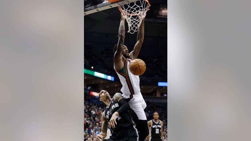 Milwaukee Bucks' Larry Sanders, top, dunks over San Antonio Spurs' Danny Green during the first half of an NBA basketball game on Wednesday, Jan. 2, 2013, in Milwaukee. (AP Photo/Morry Gash)