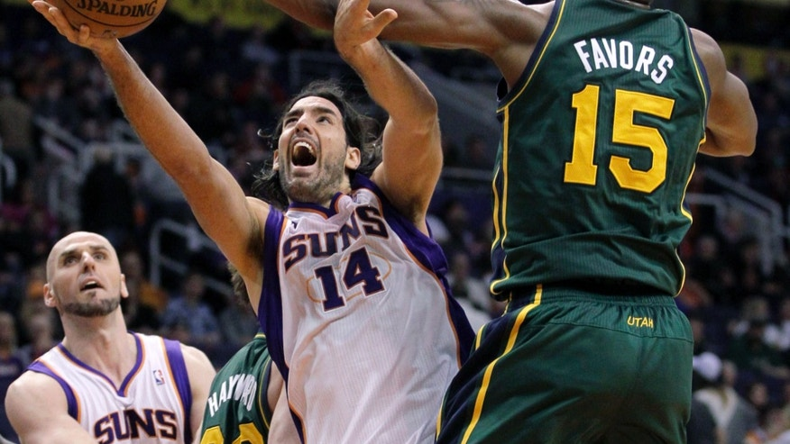 Utah Jazz forward Derrick Favors (15) fouls Phoenix Suns forward Luis Scola, of Argentina, during the first half of an NBA basketball game, Friday, Jan. 4, 2013, in Phoenix. The Jazz won 87-80. (AP Photo/Matt York)