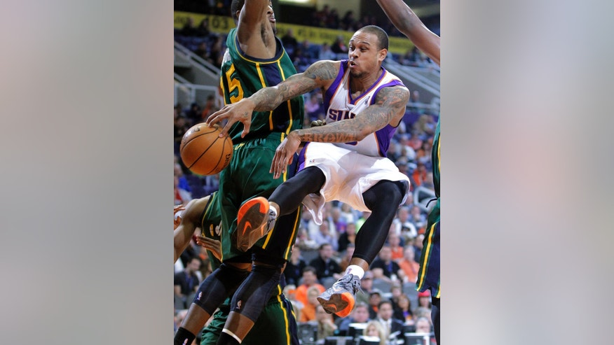 Phoenix Suns guard Shannon Brown passes around Utah Jazz forward Derrick Favors (15) during the first half of an NBA basketball game, Friday, Jan. 4, 2013, in Phoenix. The Jazz won 87-80.  (AP Photo/Matt York)