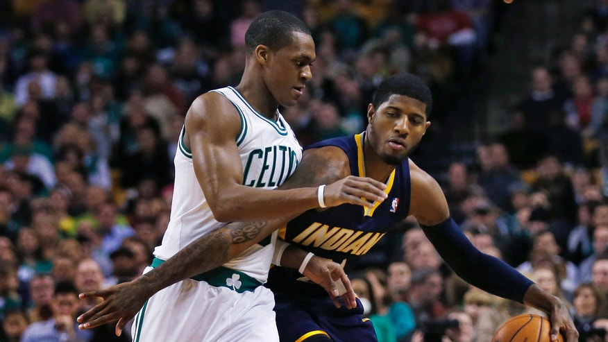 Boston Celtics guard Rajon Rondo, left. pressures Indiana Pacers forward Paul George while bringing the ball up court during the first quarter of an NBA basketball game in Boston, Friday, Jan. 4, 2013. (AP Photo/Charles Krupa)