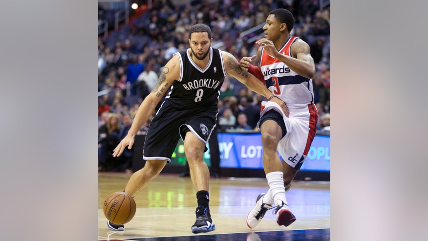 Brooklyn Nets' Deron Williams (8) drives the ball against Washington Wizards Bradley Beal (3) during the first half of an NBA basketball game in Washington, Friday, Jan. 4, 2013.  (AP Photo/Manuel Balce Ceneta)