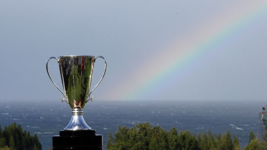 The championship trophy for the Tournament of Champions golf tournament is displayed as rainbow appears in the background, Friday morning, Jan. 4, 2013, in Kapalua, Hawaii. Tournament play begins Friday. (AP Photo/Elaine Thompson)
