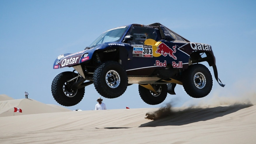 Driver Carlos Sainz of Spain and German co-driver Timo Gottschalk jump with their buggy as they compete in stage one of the 2013 Dakar Rally between Lima and Pisco, Peru,  Saturday, Jan. 5, 2013. The race finishes in Santiago, Chile, on Jan. 20. (AP Photo/Victor R. Caivano)