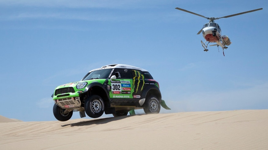 Mini driver Stephane Peterhansel of France competes in stage one of the 2013 Dakar Rally between Lima and Pisco, Peru, as a helicopter follows, Saturday, Jan. 5, 2013. The race finishes in Santiago, Chile, on Jan. 20. (AP Photo/Victor R. Caivano)