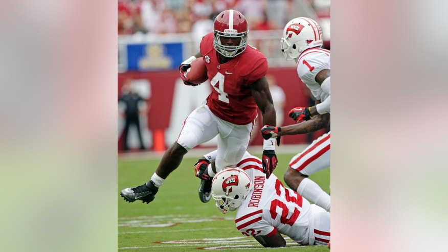 FILE - In this Sept. 8, 2012, file photo, Alabama running back T.J. Yeldon (4) is taken down after a first down run by Western Kentucky defensive back Tyree Robinson (22) and defensive back Jonathan Dowling (1) during the first half of an NCAA college football game at Bryant Denny Stadium in Tuscaloosa, Ala.  With the national championship on the line, two throwback offenses will slug it out. No. 1 Notre Dame and No. 2 Alabama rely heavily on the run, and that doesn't figure to change in the biggest game of the year. (AP Photo/Dave Martin, File)