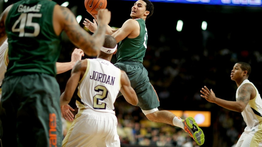 Miami's Shane Larkin, center, passes the ball to teammate Julian Gamble, left, in the first half of an NCAA college basketball game against Georgia Tech, Saturday, Jan. 5, 2013, in Atlanta. (AP Photo/David Goldman)