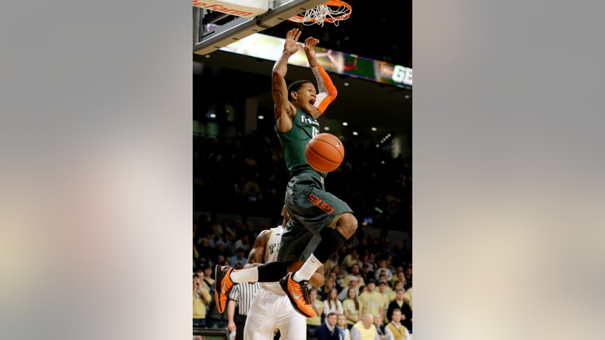 Miami's Rion Brown, center, dunks the ball in front of Georgia Tech's Marcus Georges-Hunt during the first half of an NCAA college basketball game, Saturday, Jan. 5, 2013, in Atlanta. (AP Photo/David Goldman)