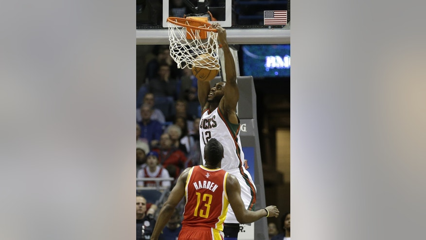 Milwaukee Bucks' Luc Richard Mbah a Moute (12) dunks as Houston Rockets' James Harden (13) defends during the first half of an NBA basketball game on Friday, Jan. 4, 2013, in Milwaukee. (AP Photo/Jeffrey Phelps)