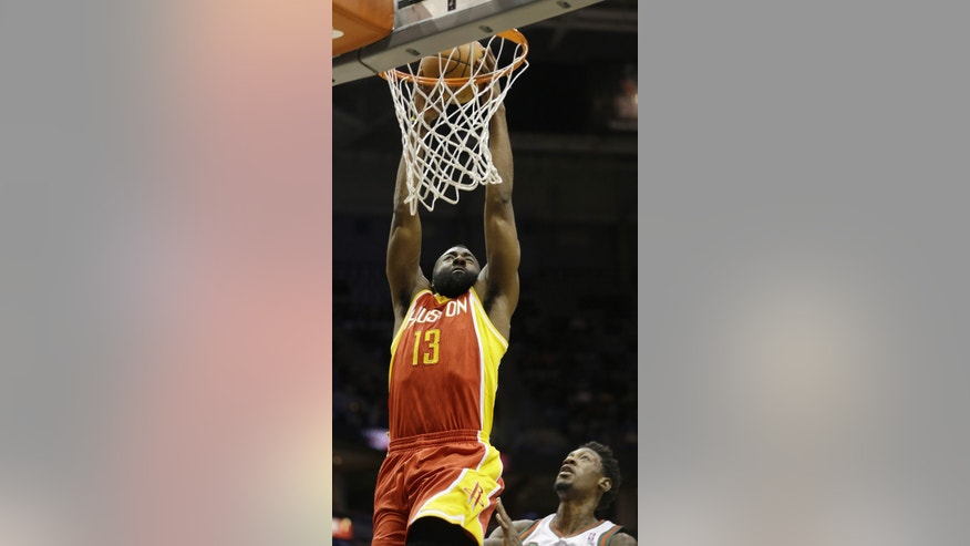Houston Rockets' James Harden (13) dunks ahead of Milwaukee Bucks' Larry Sanders during the first half of an NBA basketball game on Friday, Jan. 4, 2013, in Milwaukee. (AP Photo/Jeffrey Phelps)