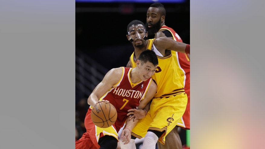 Houston Rockets' Jeremy Lin (7) drives past Cleveland Cavaliers' Kyrie Irving during the second quarter of an NBA basketball game Saturday, Jan. 5, 2013, in Cleveland. (AP Photo/Tony Dejak)