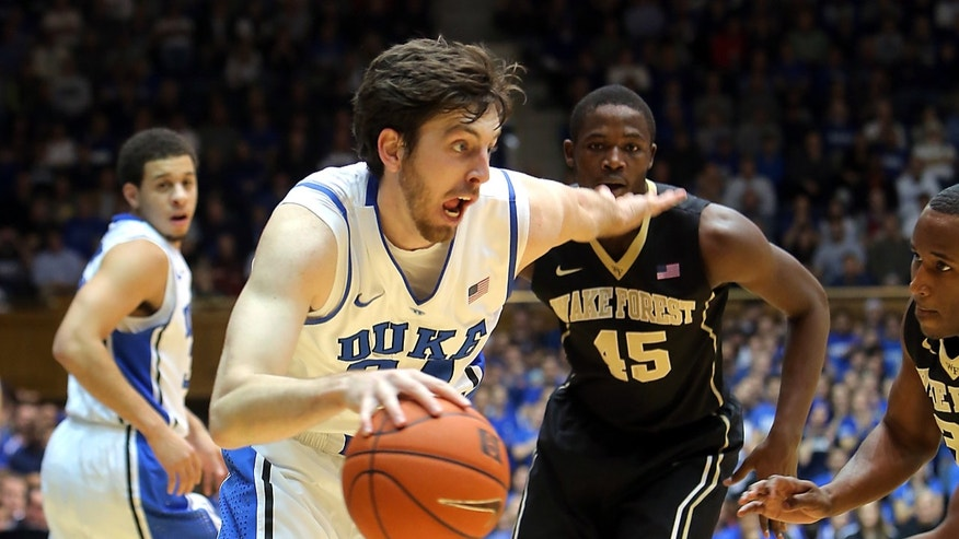 Duke's Ryan Kelly drives past Wake Forest's Amaud William Adala Moto (45) and Travis McKie, right, during the first half of an NCAA college basketball game in Durham, N.C., Saturday, Jan. 5, 2013. (AP Photo/Ted Richardson)