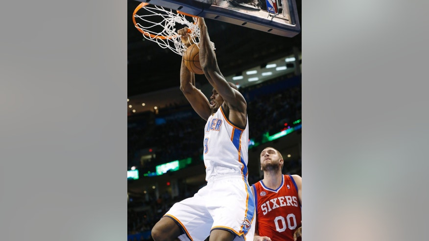 Oklahoma City Thunder forward Serge Ibaka (9) dunks in front of Philadelphia 76ers forward Spencer Hawes (00) in the fourth quarter of an NBA basketball game in Oklahoma City, Friday, Jan. 4, 2013. Oklahoma City won 109-85. (AP Photo/Sue Ogrocki)