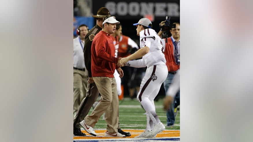 Oklahoma head coach Bob Stoops, left, and Texas A&M's Johnny Manziel, right, shake hands after the Cotton Bowl NCAA college football game Friday, Jan. 4, 2013, in Arlington, Texas. A&M won 41-13. (AP Photo/Tony Gutierrez)