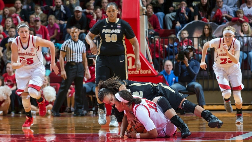 Purdue's KK Houser (22) and Nebraska's Brandi Jeffery scramble for a loose ball in the first half while Nebraska's Emily Cady (23) and Jordan Hooper (35) and Purdue's Taylor Manuel (50) run to assist during an NCAA college basketball game Saturday, Jan. 5, 2013, in Lincoln, Neb. (AP Photo/The Omaha World-Herald, Mark Davis)  MAGS OUT  LOCAL TV OUT