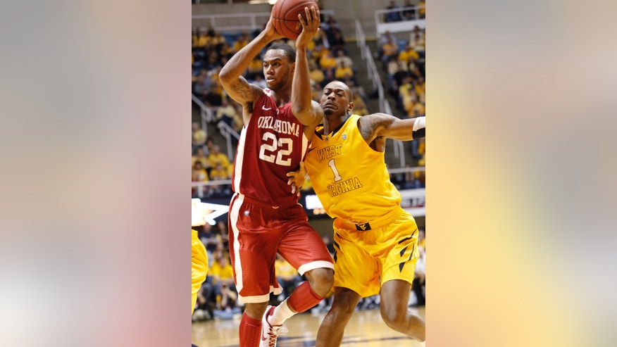 West Virginia's Dominique Rutledge, right, collides with Oklahoma's Amath M'Baye during an NCAA college basketball game in Morgantown, W.Va., Saturday, Jan. 5, 2013. Oklahoma won 67-57. (AP Photo/Randy Snyder)