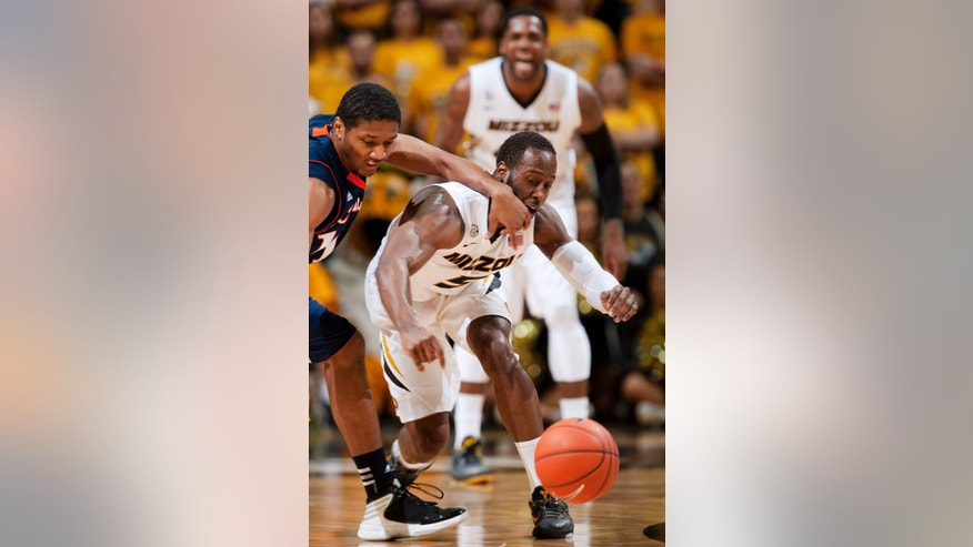 Bucknell's Ryan Hill, left, hits Missouri's Keion Bell, right, as they scramble for a loose ball during the first half of an NCAA college basketball game on Saturday, Jan. 5, 2013, in Columbia, Mo. Hill was called for a foul on the play. (AP Photo/L.G. Patterson)