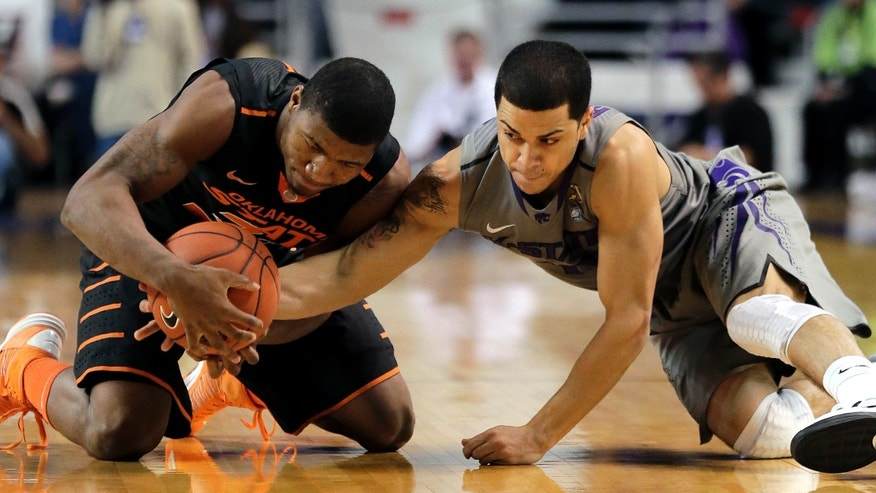 Oklahoma State guard Marcus Smart, left, and Kansas State guard Angel Rodriguez battle for the loose ball during the first half of an NCAA college basketball game, Saturday, Jan. 5, 2013, in Manhattan, Kan. (AP Photo/Charlie Riedel)