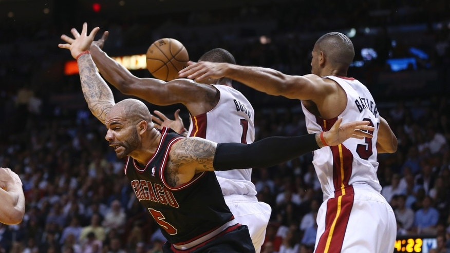 Miami Heat players Chris Bosh and Shane Battier (31) chases the ball after they blocked a shot by Chicago Bulls Carlos Boozer (5) during the second half of a NBA basketball game in Miami, Friday, Jan. 4, 2013. The Bulls won 96-89. (AP Photo/J Pat Carter)