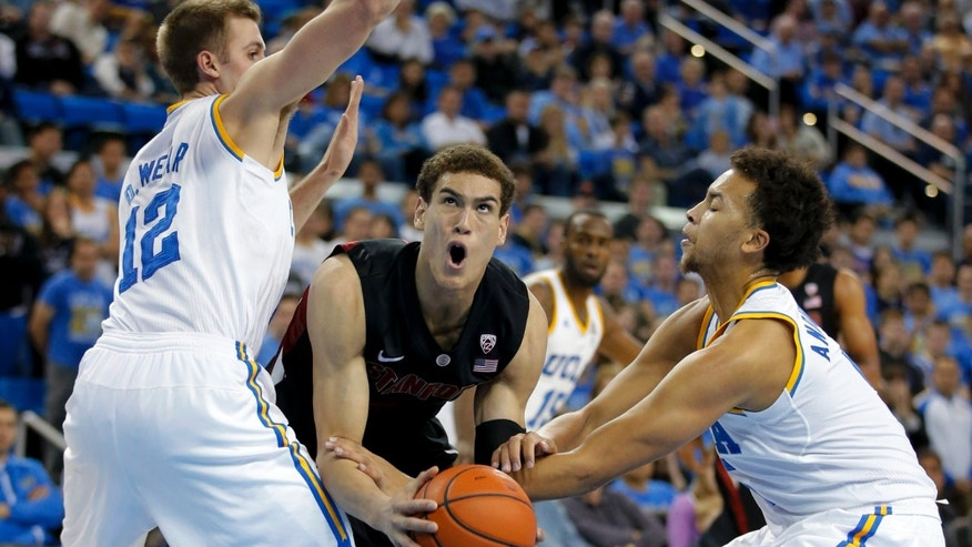 Stanford's Dwight Powell, center, looks to shoot as he is defended by UCLA's David Wear, left, and Kyle Anderson during the first half of an NCAA college basketball game in Los Angeles, Saturday, Jan. 5, 2013. (AP Photo/Jae C. Hong)