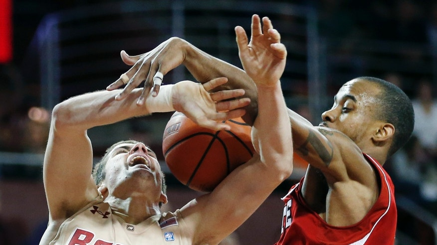 North Carolina State's Lorenzo Brown, right, fouls Boston College's Joe Rahon (25) in the second half of an NCAA college basketball game in Boston, Saturday, Jan. 5, 2013. (AP Photo/Michael Dwyer)