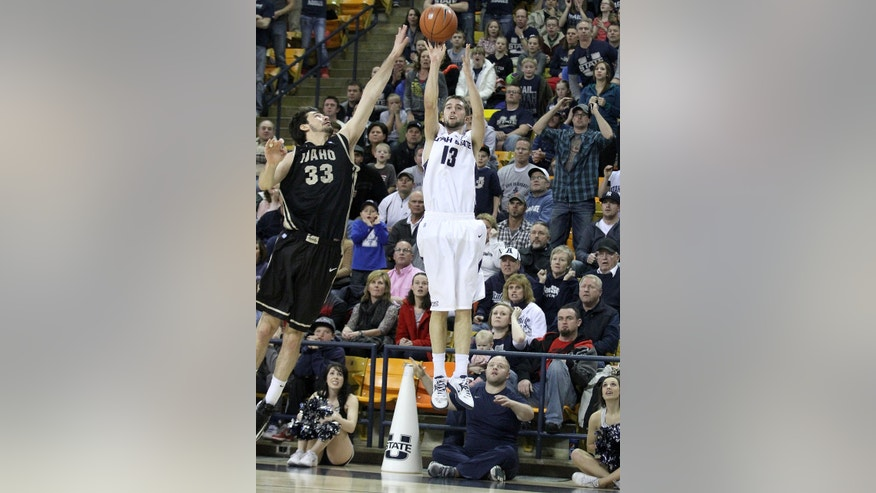 Utah State's Preston Medlin (13) takes a 3-point shot while being guarded by Idaho's Kyle Barone during an NCAA college basketball game Saturday, Jan. 5, 2013, in Logan, Utah. Medlin's shot was good and sent the game into overtime. (AP Photo/The Herald Journal, John Zsiray)