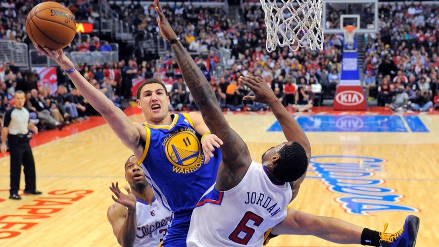 Golden State Warriors guard Klay Thompson, center, shoots against Los Angeles Clippers center DeAndre Jordan (6) as Clippers guard Willie Green watches during the first half of their NBA basketball game, Saturday, Jan. 5, 2013, in Los Angeles.  (AP Photo/Mark J. Terrill)