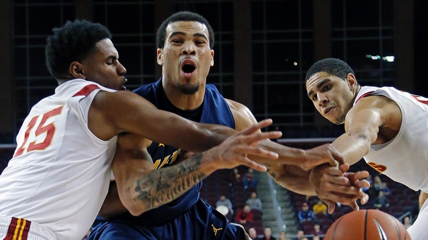 California guard Justin Cobbs ( 1) tries to break through the defense of Southern California guard Brendyn Taylor (15) and forward Aaron Fuller (21) in the first half of an NCAA college basketball game in Los Angeles on Saturday, Jan. 5, 2013. (AP Photo/Reed Saxon)