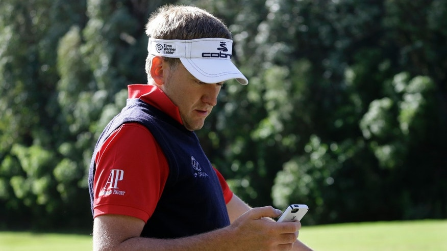Ian Poulter, of England, looks on his cell phone for updates on the event status while on the driving range at the Tournament of Champions PGA golf tournament, Saturday, Jan. 5, 2013, in Kapalua, Hawaii. He had announced moments earlier to fans looking on that he believed that within minutes it would be announced that play for the day would be canceled. Because of wind, play was canceled for the day after being stopped a day earlier. It has been re-scheduled to begin on Sunday. (AP Photo/Elaine Thompson)