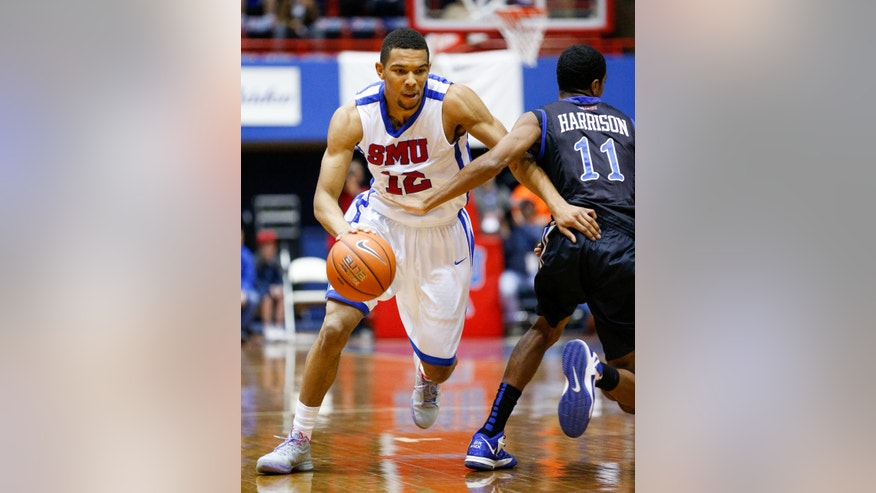 SMU's Nick Russell (12) drives to the basket around Tulsa's Shaquille Harrison (11) during an NCAA college basketball game, Sunday, Jan. 6, 2013, in Dallas. (AP Photo/The Dallas Morning News, Stan Olszewski)  MANDATORY CREDIT; MAGS OUT; TV OUT; INTERNET OUT; AP MEMBERS ONLY.