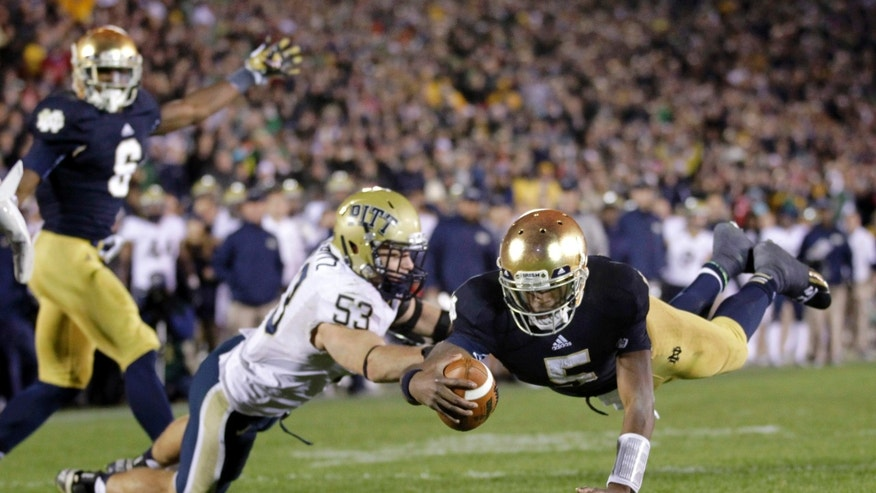FILE - In this Nov. 3, 2012, file photo, Notre Dame quarterback Everett Golson dives into the end zone in front of Pittsburgh linebacker Joe Trebitz for a 2-point conversion to tie the game late in the fourth quarter against Pittsburgh in an NCAA college football game in South Bend, Ind. Notre Dame defeated Pittsburgh 29-26 in triple overtime.  No. 1 Notre Dame enjoyed its share of fortunate breaks on its way to the BCS title game scheduled for Monday, Jan. 7, 2013, with perhaps the bulk of those coming during a wild game at home against Pittsburgh. And without those breaks, Notre Dame would be out of the title chase. (AP Photo/Michael Conroy, File)