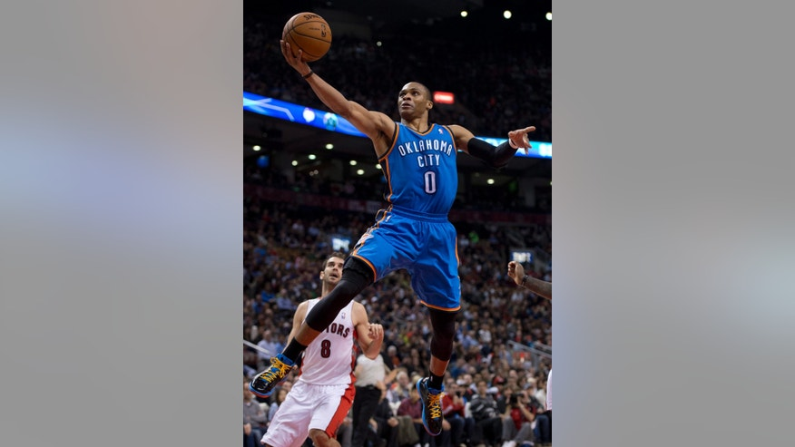 Toronto Raptors guard Jose Calderon (8) watches as Oklahoma City Thunder guard Russell Westbrook jumps to the hoop during first-half NBA basketball game action in Toronto, Sunday, Jan.6, 2013. (AP Photo/The Canadian Press, Frank Gunn)