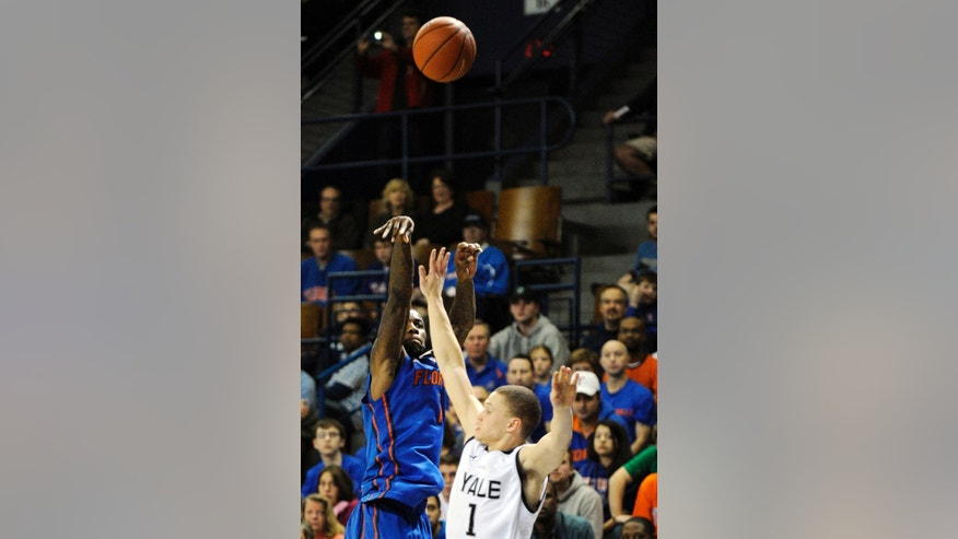 Florida's Kenny Boynton, left, shoots over Yale's Austin Morgan during the first half of an NCAA college basketball game in New Haven, Conn., Sunday, Jan. 6, 2013. Boynton matched his career high with 28 points as Florida won 79-58. (AP Photo/Fred Beckham)