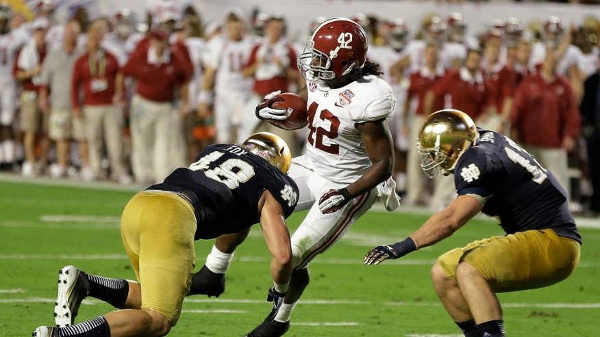 Alabama's Eddie Lacy spins past Notre Dame's Dan Fox (48) and Danny Spond for a touchdown during the first half of the BCS National Championship college football game Monday, Jan. 7, 2013, in Miami. (AP Photo/Chris O'Meara)