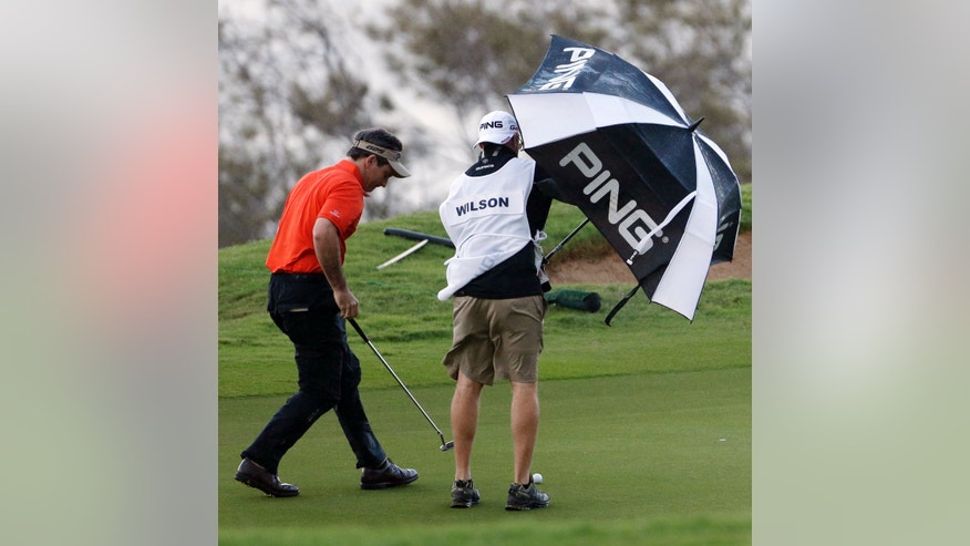 A caddy uses an umbrella to block the wind as Mark Wilson lines up a putt on the 12th hole during the first round at the Tournament of Champions PGA golf tournament Monday, Jan. 7, 2013 in Kapalua, Hawaii. Play was to have started three days earlier, but was delayed because of rain and high winds. (AP Photo/Elaine Thompson)