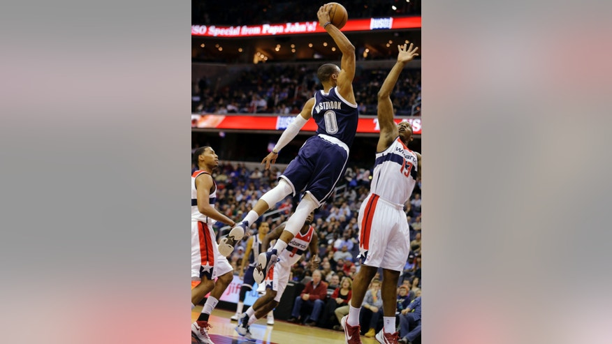 Oklahoma City Thunder guard Russell Westbrook goes for the dunk over Washington Wizards forward Kevin Seraphin (13), from France, in the first half of an NBA basketball game Monday, Jan. 7, 2013, in Washington. (AP Photo/Alex Brandon)