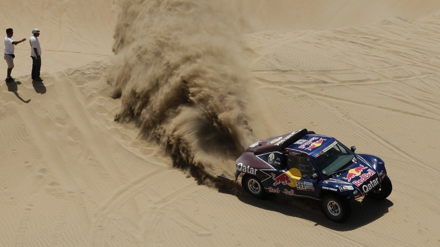 Driver Carlos Sainz of Spain and German co-driver Timo Gottschalk compete in the 3nd stage of the 2013 Dakar Rally from Pisco to Nazca, Peru, Monday, Jan. 7, 2013. The race finishes in Santiago, Chile, on Jan. 20. (AP Photo/Victor R. Caivano)