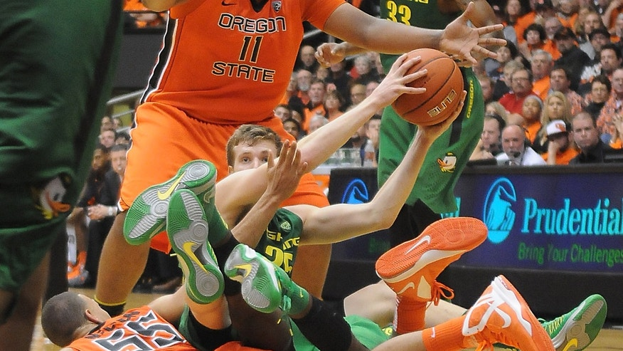 Oregon's E.J. Singler looks for an open teammate after tumbling over Oregon State's Roberto Nelson for a loose ball during the Civil War game Sunday January Jan. 6, 2013 at Gill Coliseum in Corvallis, Ore. (AP Photo/Jesse Skoubo, Corvallis Gazette-Times)
