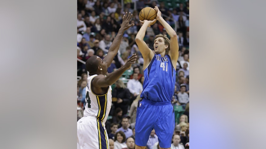 Dallas Mavericks forward Dirk Nowitzki (41) shoots as Utah forward Paul Millsap defends in the first quarter during an NBA basketball game Monday, Jan. 7, 2013, in Salt Lake City. (AP Photo/Rick Bowmer)