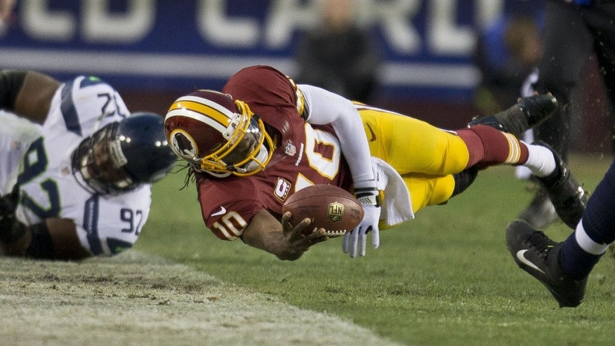 Washington Redskins quarterback Robert Griffin III dives for a first down in the first half of an NFL football wild card playoff game against the Seattle Seahawks on Sunday, Jan. 6, 2013, in Landover, Md. (AP Photo/The Seattle Times, Dean Rutz) SEATTLE OUT  MAGS OUT  NO SALES  MANDATORY CREDIT  TV OUT  USA TODAY OUT