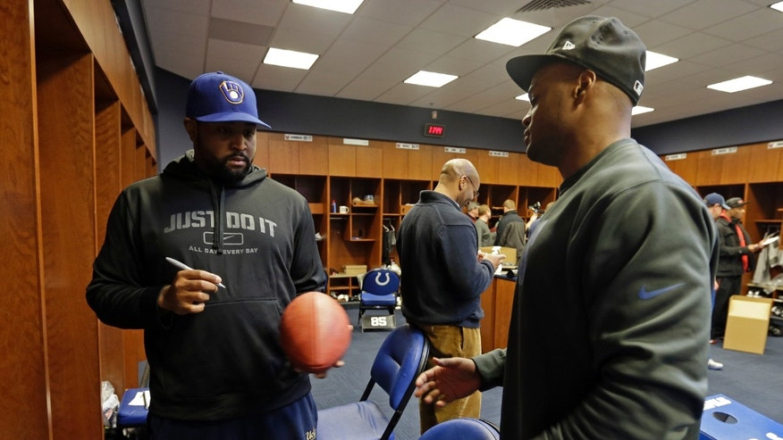 Indianapolis Colts' Justin Hickman, left, hands a football to Jerrell Freeman after autographing it for Freeman at the Colts complex Monday, Jan. 7, 2013, in Indianapolis. The Colts were defeated by the Baltimore Ravens, 24-9, in a NFL football wild card playoff game on Sunday. (AP Photo/Darron Cummings)