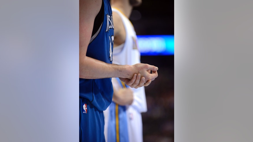 Minnesota Timberwolves forward Kevin Love (42) holds his injured right hand during the third quarter of an NBA basketball game against the Denver Nuggets, Thursday, Jan. 3, 2013, in Denver. (AP Photo/Jack Dempsey)