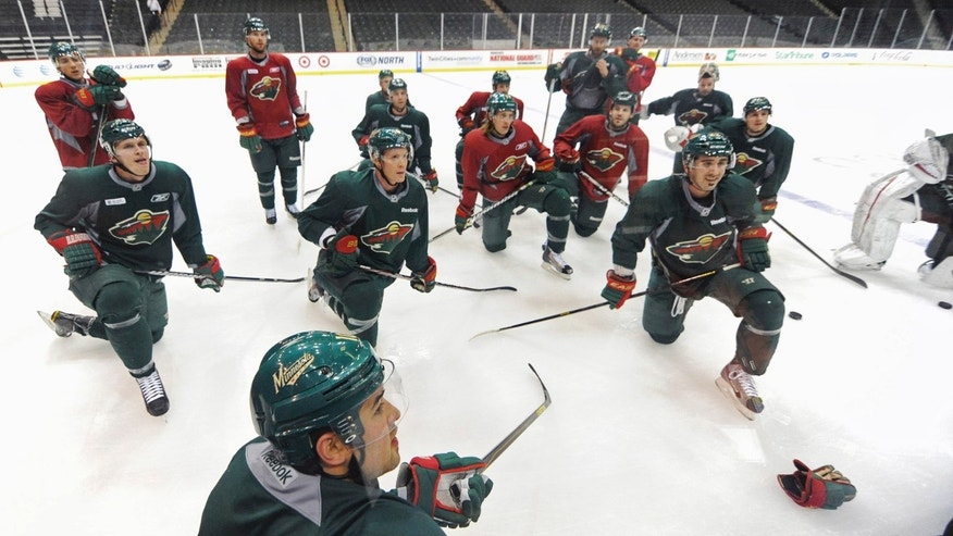 Minnesota Wild NHL hockey players, including Devin Setoguchi, foreground, listen to instructions from an organizational instructor after they returned Monday, Jan. 7, 2013, for an informal workout at the Xcel Arena in St. Paul, Minn., for the first time since a tentative agreement was reached in the NHL lockout. (AP Photo/Jim Mone)