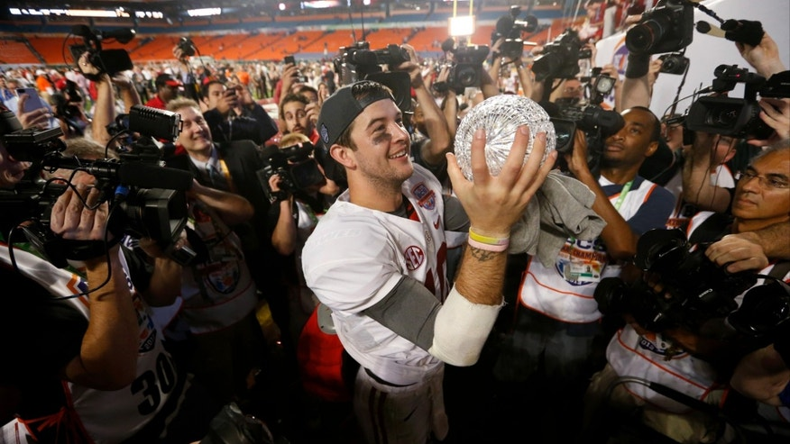 Alabama's AJ McCarron holds The Coaches Trophy after the BCS National Championship college football game against Notre Dame Monday, Jan. 7, 2013, in Miami. Alabama won 42-14. (AP Photo/John Bazemore)
