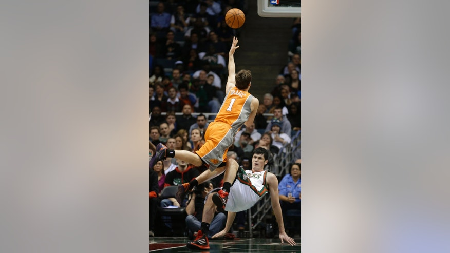 Phoenix Suns' Goran Dragic (1) is fouled by Milwaukee Bucks' Ersan Ilyasova, bottom, during the second half of an NBA basketball game Tuesday, Jan. 8, 2013, in Milwaukee. (AP Photo/Jeffrey Phelps)