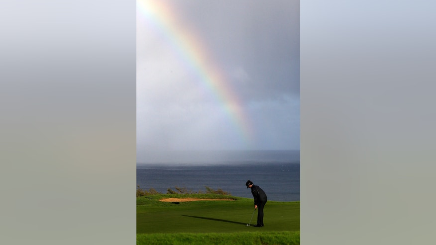 Bubba Watson putts in view of a rainbow behind on the 13th hole during the first round at the Tournament of Champions PGA golf tournament, Monday, Jan. 7, 2013, in Kapalua, Hawaii. Play was to have started three days earlier, but was delayed because of rain and high winds. (AP Photo/Elaine Thompson)