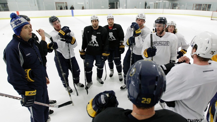 Former Buffalo Sabres player Andrew Peters, left, and Sabres players chat during an NHL hockey workout in Amherst, N.Y., Tuesday, Jan. 8, 2013. (AP Photo/David Duprey)