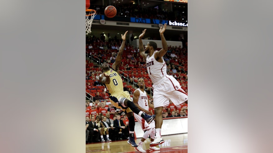 North Carolina State's Richard Howell (1) defends as Georgia Tech's Mfon Udofia (0) drives to the basket during the second half of an NCAA college basketball game in Raleigh, N.C., Wednesday, Jan. 9, 2013. North Carolina State won 83-70. (AP Photo/Gerry Broome)