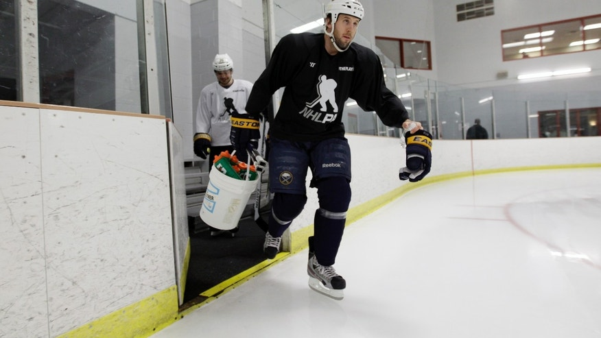 Buffalo Sabres' Matt Ellis skates onto the ice with a bucket of pucks and water bottles during NHL hockey practice in Amherst, N.Y., Tuesday, Jan. 8, 2013. (AP Photo/David Duprey)